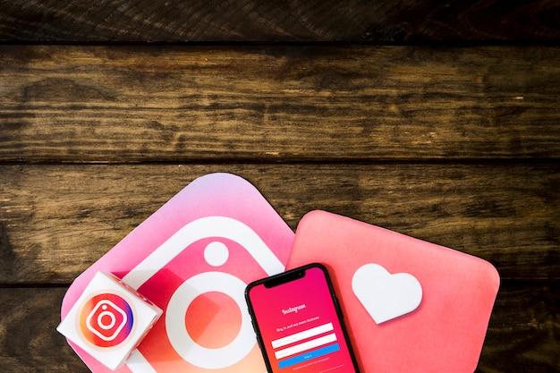 木製テーブル上の携帯電話とinstagramインターフェイス