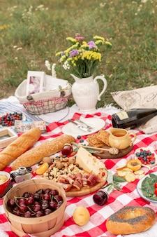Стильный пикник на зеленой лужайке. свежие круассаны и чайник с чаем на покрывале возле плетеной женской шапки. instagram контент