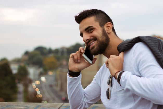 Красивый человек, разговор по телефону на открытом воздухе. с кожаной курткой, солнечными очками, парнем с бородой. эффект instagram