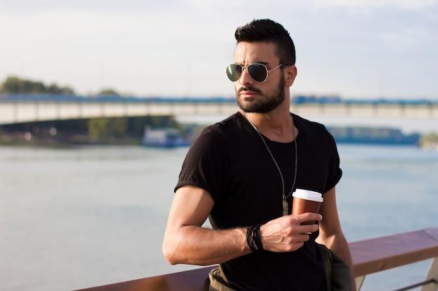 屋外でコーヒーを飲むハンサムな男。ひげそりを持つ男サングラス。 instagramエフェクト。