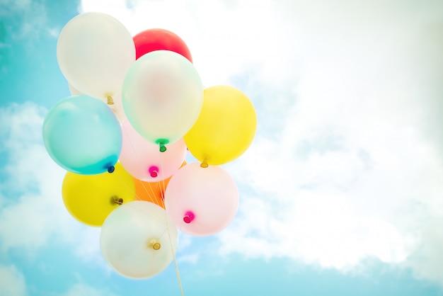 ヴィンテージの多色風船は青い空にレトロなinstagramフィルター効果で行われます。夏とバレンタイン、結婚式の新婚旅行の概念で愛の背景のためのアイデア。
