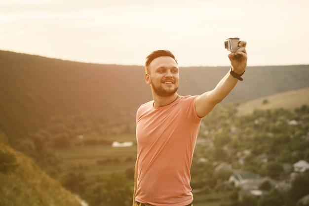 ハンサムな男がアクションカメラで自己の写真を撮る。レトロなビンテージinstagramフィルター