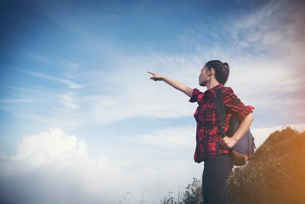 Женщина-путешественник свободы, стоя с поднятыми руками и наслаждаясь красивой природой. изображение с фильтром instagram