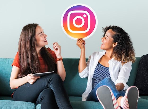 Молодые женщины, показывая значок instagram