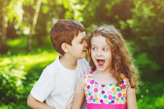 Удивлен, маленькая девочка и мальчик, разговаривая с шепотом. тонировка в фильтр instagram.