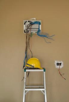 壁の背景と安全ヘルメットに電気ボックス サーキット ブレーカー ボードの配線を取り付けます。