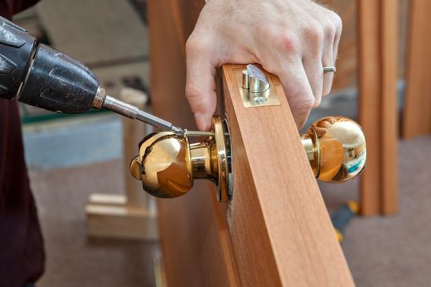 자물쇠가 달린 문 손잡이를 설치하고 목수는 전기 드릴 드라이버를 사용하여 나사를 조입니다.