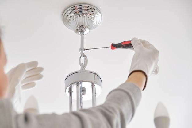 設置天井ランプ、プロのツールを使用してシャンデリアを固定する電気技師の手