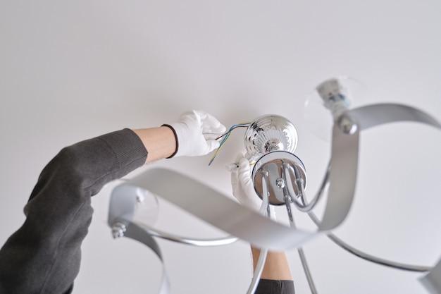 Установка потолочного светильника, руки мужчины-электрика, устанавливающего люстру с помощью профессиональных инструментов.