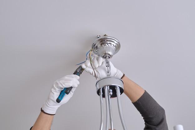 設置天井ランプ、プロのツールを使用してシャンデリアを固定する男性の電気技師の手