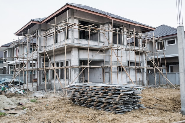 Installation of cement formwork frames to new house construction at building site, real estate development