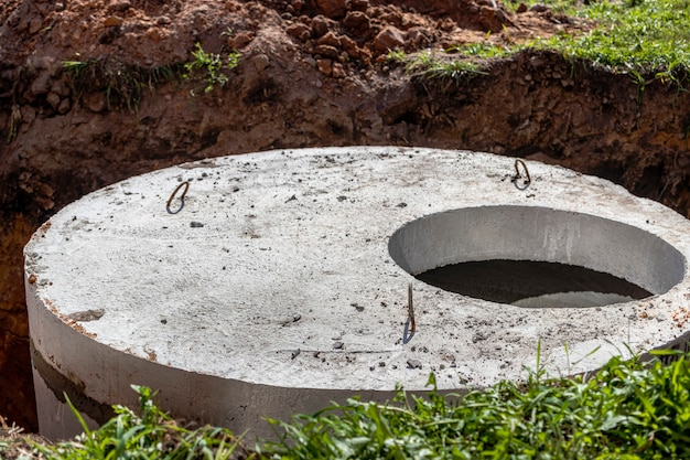 Installation of concrete sewer wells in the ground at the construction site. the use of reinforced concrete rings for cesspools, overflow septic tanks. improvement of wells and storm sewage.