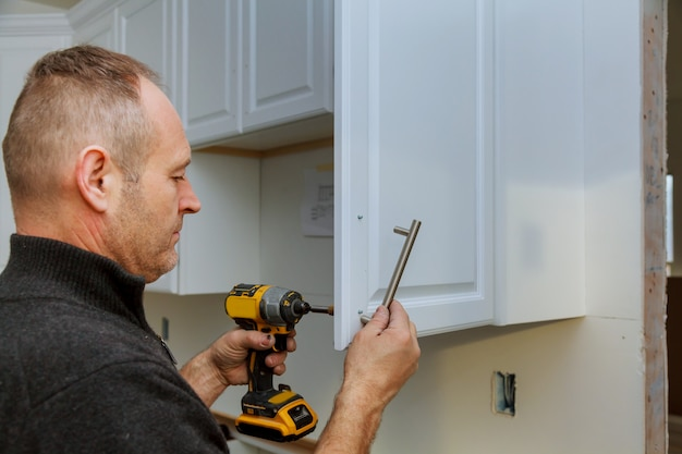Installation of door handles on kitchen cabinets with a screwdriver