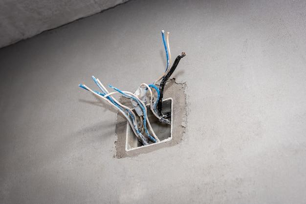 コンクリート壁にコンセントとワイヤーを取り付けるための電気ボックス。