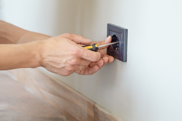 Installation of electrical sockets in closeup of hand of electrician installing wall outlet.