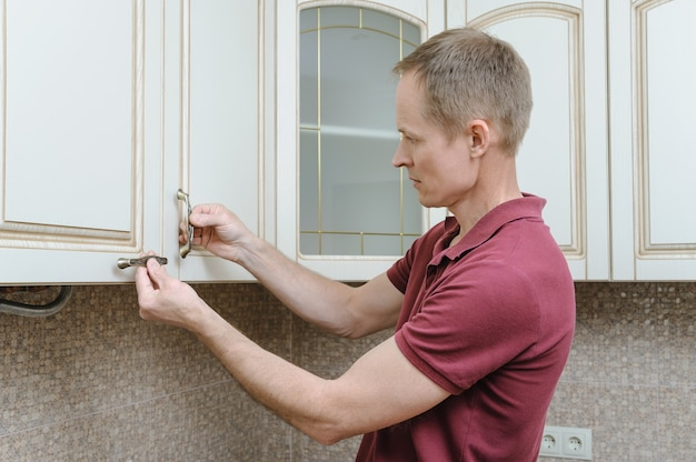 Installation of kitchen furniture putting handles to door cabinets