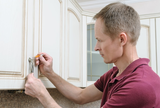 Installation of kitchen furniture with a pencil to fix the door handle of the cabinet