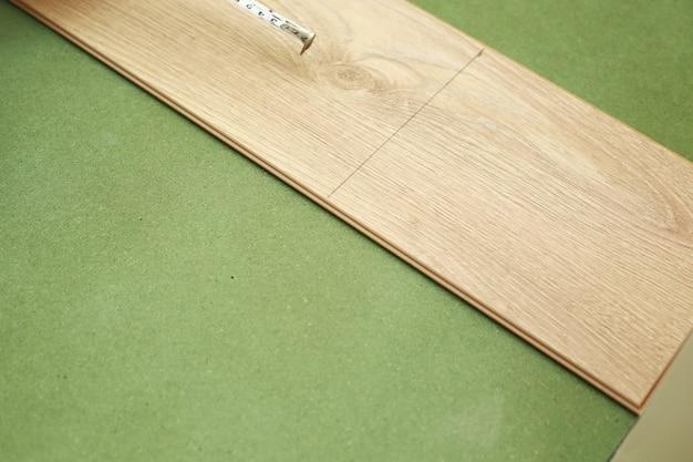 Укладка ламината или паркета в комнате, рабочий укладывает деревянный ламинат, размечает длину ламината. укладка ламината дома. измерение с помощью рулетки.