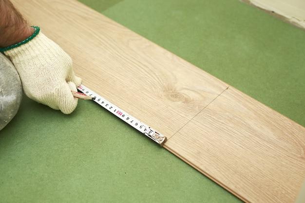 Укладка ламината или паркета в комнате, рабочий укладывает деревянный ламинат, размечает длину ламината. укладка ламината дома. мужчина измеряет и маркирует.
