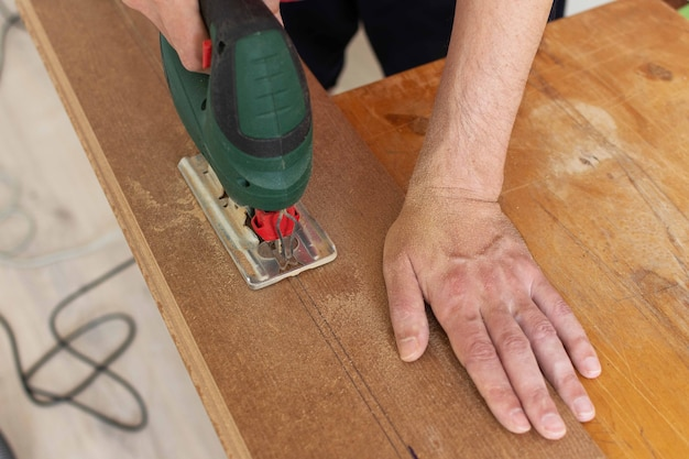 Installation laminate or parquet in the room, worker cuts a laminate of a certain length with a jigsaw