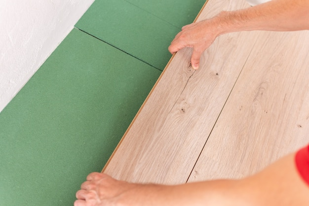 Installation laminate or parquet in the room, worker installing wooden laminate flooring