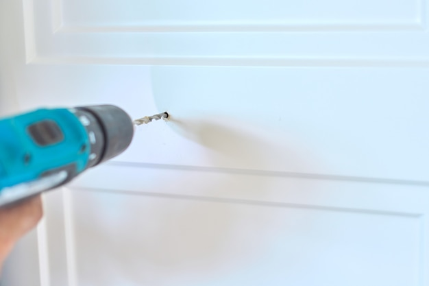 Installation of new cabinet, close-up of hands of working carpenter craftsman with tool, handyman makes holes with drill for attaching door handles