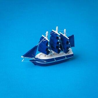 青い背景に帆を備えた青いヨットの設置。旅行と冒険の概念。