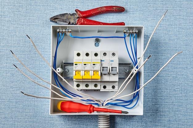 自動ヒューズ付きの家庭用電気パネルまたはヒューズボックスの設置。修理工が配電盤または分電盤に作業工具を置き忘れました。家庭用配線へのサーキットブレーカの設置。