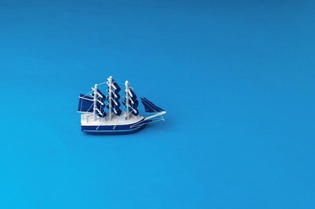 青い帆が海に浮かぶ帆船の設置。旅行と冒険の概念。