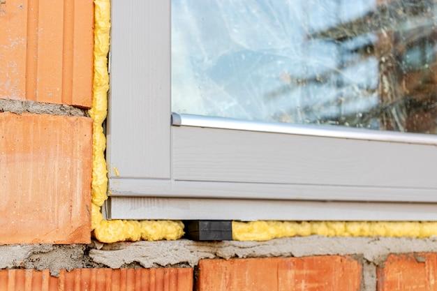 れんが造りの建物に窓を設置する。インダストリアル・エンジニアリング。ポリウレタンフォームを使用した窓の開口部の暗化と設置。 Premium写真