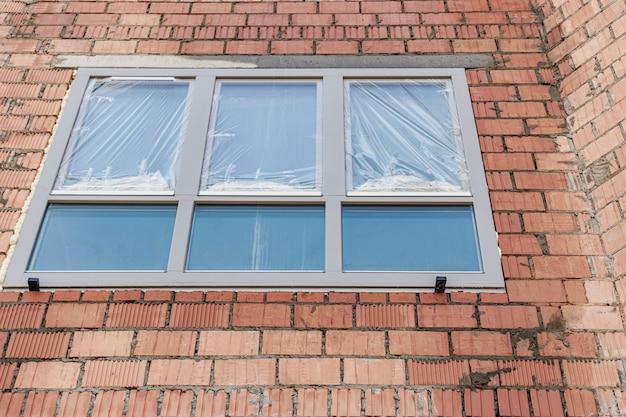 れんが造りの建物に窓を設置する。インダストリアル・エンジニアリング。ポリウレタンフォームを使用した窓の開口部の暗化と設置。