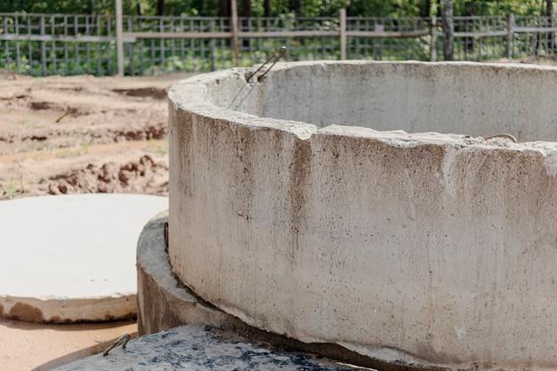 建設現場の地面にコンクリート下水道井戸を設置。セスプール、オーバーフロー浄化槽に鉄筋コンクリートリングを使用。井戸と雨水管の改良。