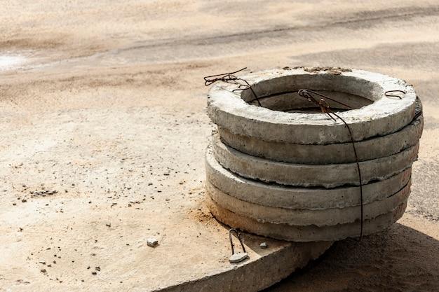 건설 현장의 땅에 콘크리트 하수구 설치. cesspool, 오버플로 정화조에 철근 콘크리트 링 사용. 우물 및 폭풍우 하수 개선.