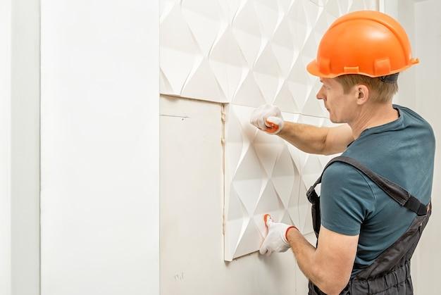 Монтаж гипсовой 3d панели. рабочий прикрепляет гипсовую плитку к стене.