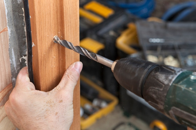 Установка межкомнатных дверей, крупным планом просверливание отверстия в деревянной рамке электрическим сверлом.