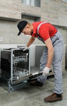 주방 설치. 작업자가 식기세척기를 제자리에 놓습니다.