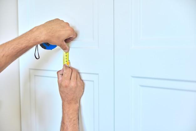 Установка нового шкафа, крупный план рук рабочего плотника с инструментом, мастер намечает место крепления дверных ручек