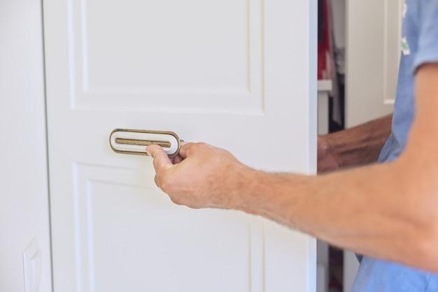 Установка нового шкафа, крупный план рук рабочего плотника с инструментом, мастер устанавливает дверные ручки