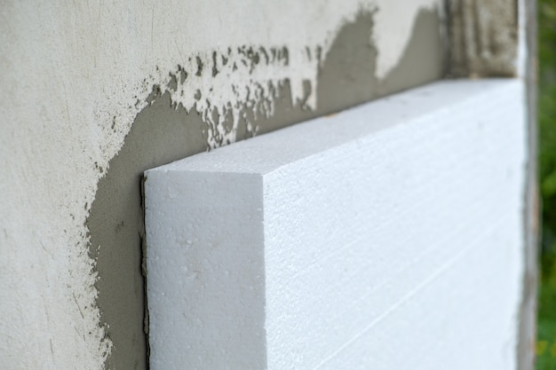 Монтаж листов пенополистирола на стене фасада дома для тепловой защиты.