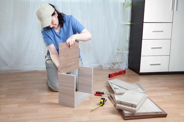 집에 파티클 보드로 만든 목재 가구 설치, 여성은 서랍을 조립합니다.