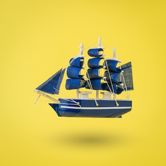 Installation of an old ship with sails on a yellow surface. a dream come true.