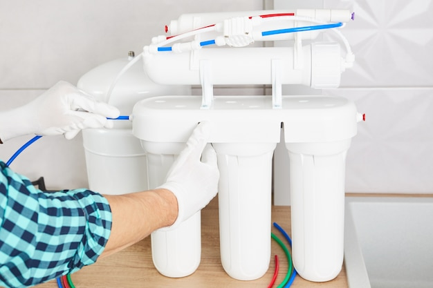 Installation osmosis system. plumber hand replace water filter cartridges at home kitchen.