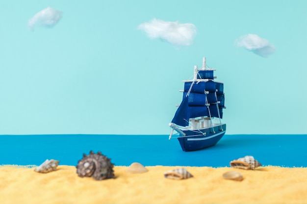 Installation of a sailboat moored to a sandy beach with seashells. the concept of travel and adventure. installation.