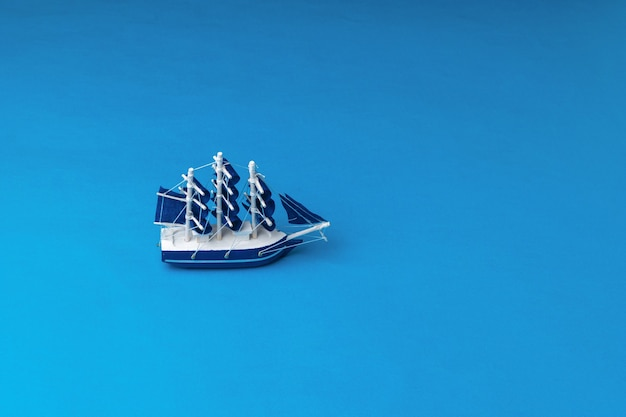 Installation of a sailboat with blue sails floating on the sea. the concept of travel and adventure.