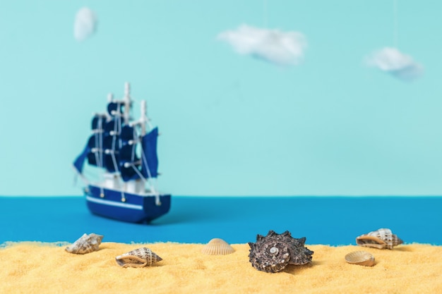 Installation of seashells on a sandy beach against the backdrop of a sailing ship sailing away. the concept of travel and adventure. installation.