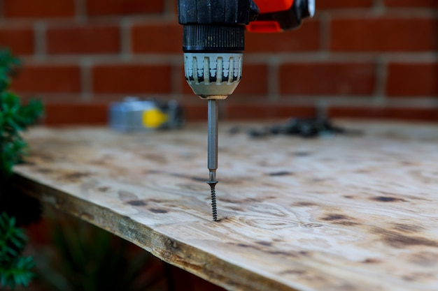 Installation of wood worker twisting screw into the wood board.