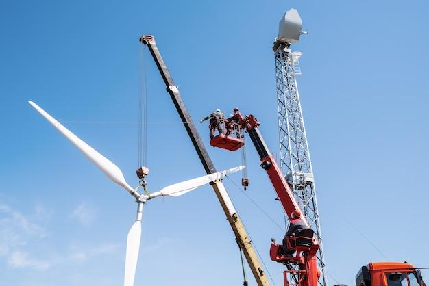 Установщики используют автокран и автовышку для подъема ротора ветряной турбины.
