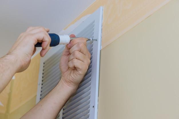 Установка крышки вентиляционного отверстия на стене с помощью отвертки