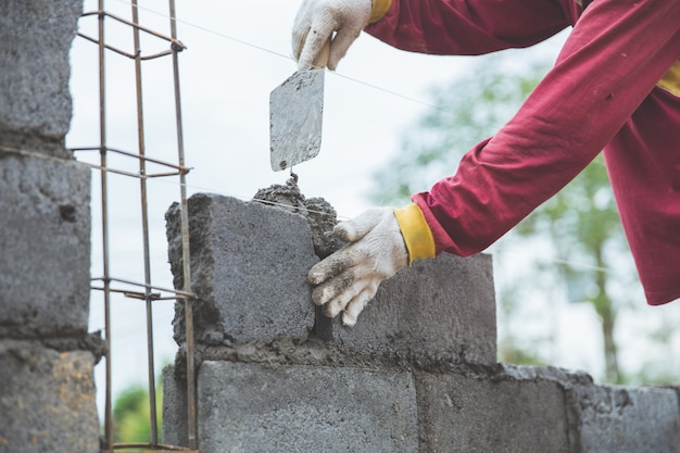 Installing cement bricks on construction site