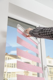 Installing fabric roller blinds.